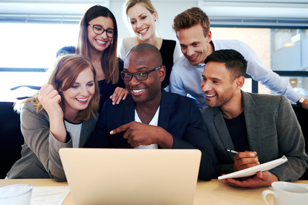 gathered: Black male executive smiling at camera with colleagues gathered around him and laptop