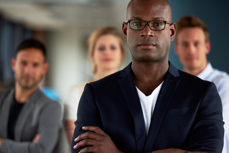 woman pose: Black male executive with arms crossed and serious expression facing camera with colleagues in background