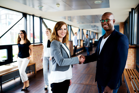 White female executive and black male executive shaking hands in hallway and smiling at camera Stock Photo