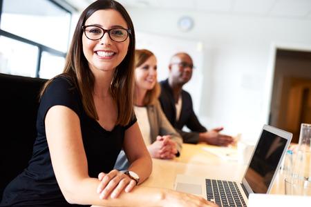 the working day: Hembra joven blanco sonriente durante la reunión en la sala de conferencias de la oficina ejecutiva Foto de archivo