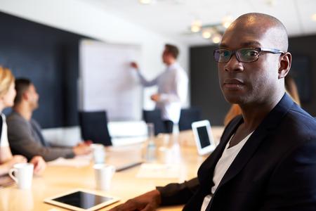persone nere: Nero Esecutivo maschio fronte fotocamera con un'espressione seria nel corso della riunione Archivio Fotografico