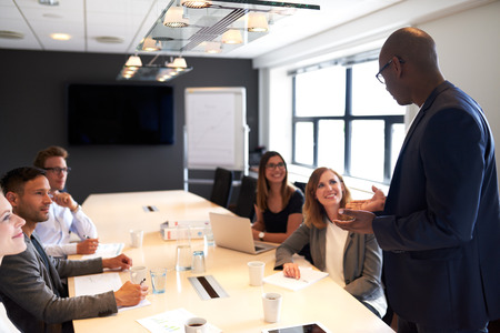 executive women: Black man leading a meeting with a group of executives in a conference room Stock Photo