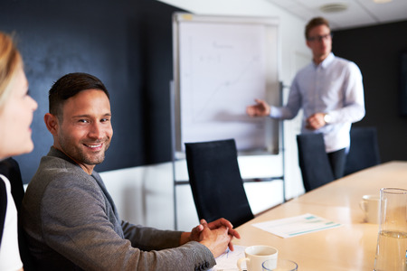 facing on camera: Young white male executive smiling and facing camera during work meeting