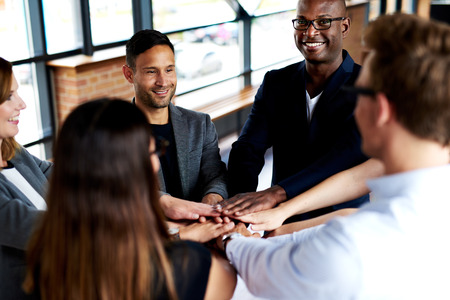 camaraderie: Group of young executives smiling and standing together with hands together Stock Photo