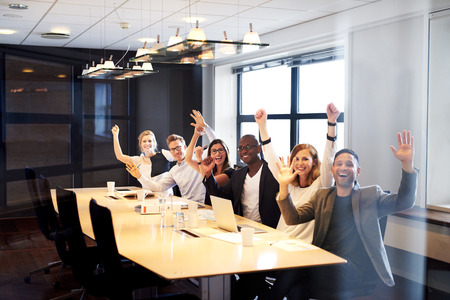 Group of young executives sitting at conference table posing with arms in air for camera.