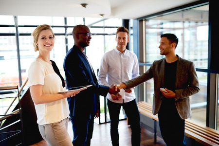introduction: Group of young executives in modern space smiling and making introductions. Stock Photo