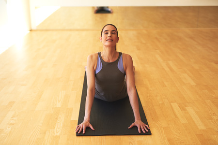 concentrates: Thoughtful Healthy Young Woman Doing Stretching Exercise with Eyes Closed on Yoga Mat In Front of the Camera.