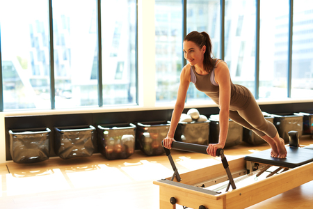 pilates studio: Healthy Smiling Brunette Woman Wearing Leotard and Practicing Pilates in Exercise Studio