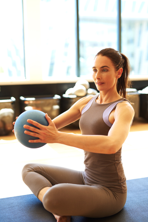 Good looking brunette is exercising her arms with med ball