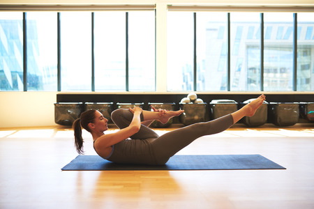 Young woman is stretching her left knee 스톡 콘텐츠