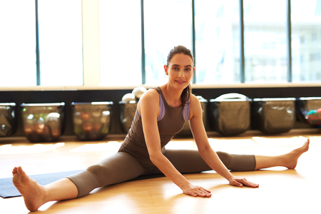 suppleness: Young woman is finishing her pilates class doing stretching Stock Photo