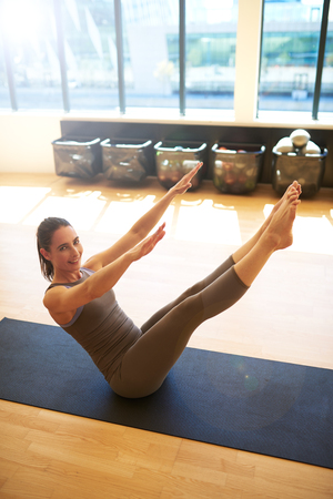centering: Good looking woman is doing sit ups with her arms and legs raised in the air Stock Photo