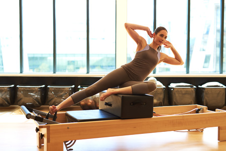 centering: Healthy Brunette Woman Wearing Leotard and Practicing Pilates in Exercise Studio