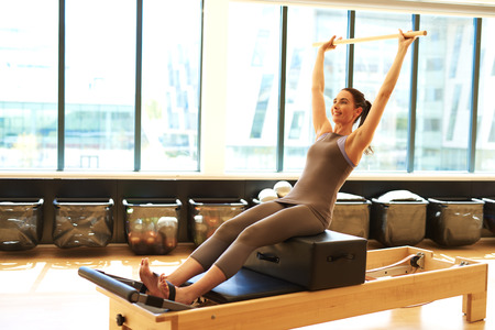 centering: Healthy Smiling Brunette Woman Wearing Leotard and Practicing Pilates in Exercise Studio