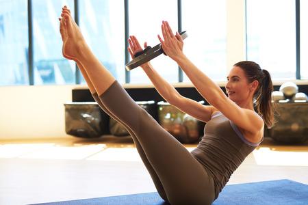 젊은 여자는 그녀의 복부 근육을 그녀의 팔 사이에 무게를 잡고 훈련한다