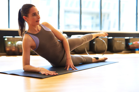 centering: Healthy Young Woman Laying on her Side on a Fitness Mat and Doing Leg Exercise at the Gym While Looking Into Distance.