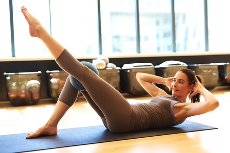centering: Good looking female is exercising the abdominal muscles using exercise ball Stock Photo