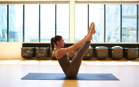Tireless woman is holding her legs with her arms to strengthen the abdominal muscles