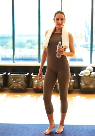 clothes: Good looking female with a bottle of water is taking a break from exercises
