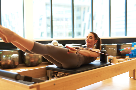 centering: Healthy Smiling Brunette Woman Wearing Leotard Practicing Pilates in Bright Exercise Studio
