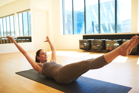 Young woman doing sit ups with her eyes closed