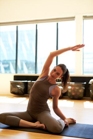 cardiovascular exercising: Attractive female is stretching while she is sitting on the floor