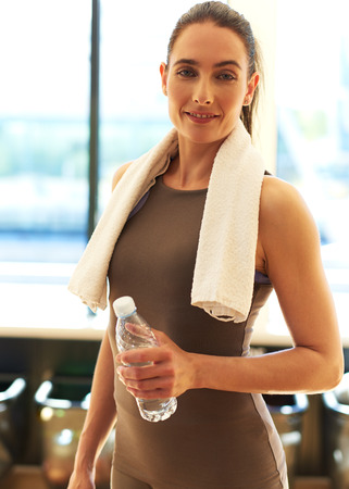 water sports: Portrait of a Fit Young Woman with White Towel on her Shoulders, Holding a Bottle of Water and Smiling at the Camera. Stock Photo