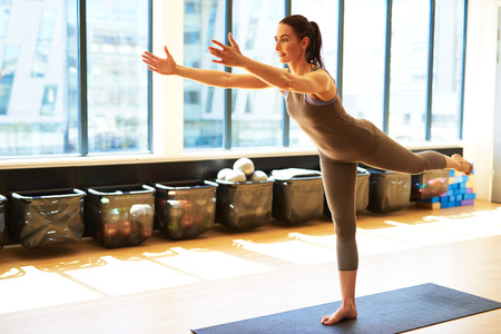 centering: Fit woman is balancing on one leg