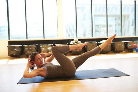 centering: Profile of Healthy Brunette Woman Wearing Leotard Practicing Pilates on Floor Mat in Bright Exercise Studio Stock Photo