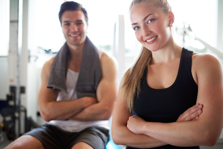 Close up Young Fit Couple Smiling at Camera After Workout inside the Gym, with Arms Crossed in front their Bodies.
