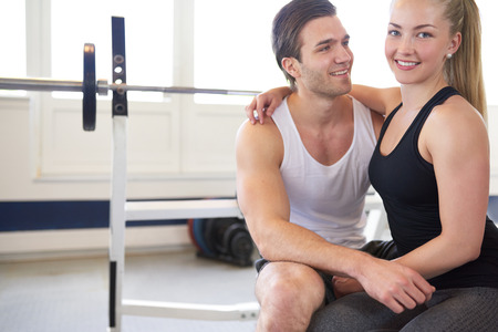 couple lit: Portrait of Loving Couple Sitting Close Together with Arms Around Each Other in Brightly Lit Gym, with Copy Space