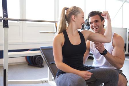 musculo: Macho Tamaño de Pruebas Entrenador de Mujer Rubia Bíceps muscular, Juguetón Pareja Comprobación Músculos y sonríen en uno a en mucha Luz Gimnasio Foto de archivo