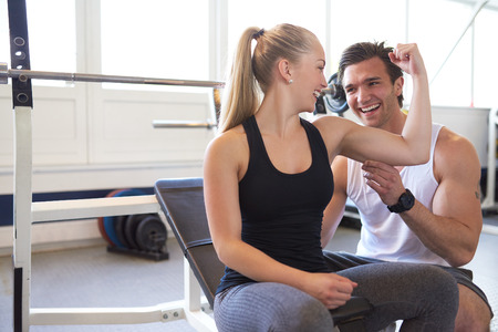 couple lit: Male Trainer Testing Size of Blond Woman Bicep Muscle, Playful Couple Checking Muscles and Smiling at Each Other in Brightly Lit Gym