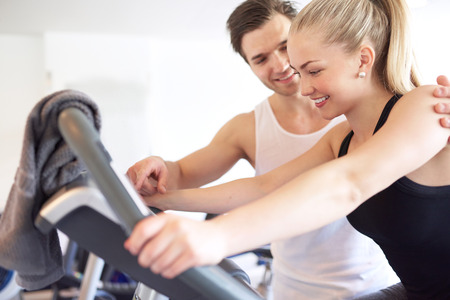 toning: Sweet Athletic Handsome Boyfriend Assisting his Pretty Girlfriend Doing an Exercise on Elliptical Bike Inside the Gym