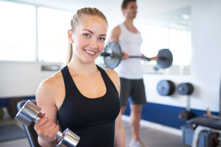 pesas: Cerrar una bonita joven activa Mujer levantando pesas en el gimnasio y sonriente a la cámara. Foto de archivo