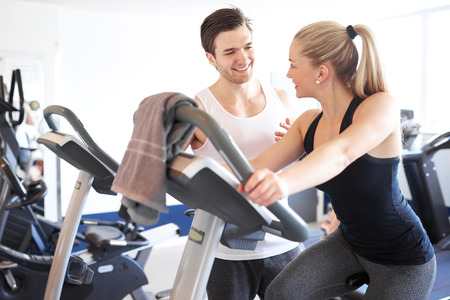 trainer device: Handsome Young Fitness Trainer Explaining Something to a Young Woman While on Elliptical Bike Device Inside the Gym Stock Photo