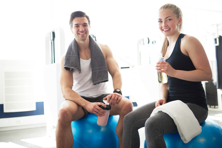 man gym: Active Young Couple Relaxing on Exercise Ball After Workout In the Gym and Smiling at the Camera