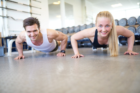 Low Angle View of Couple Doing Push Ups Together or Planking in Gym, Front View of Happy Healthy Couple Working Out Together