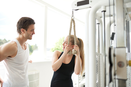 trainer device: Handsome Young Fitness Trainer Talking to a Healthy Woman After Doing an Exercise on Pulley Device Inside the Gym.