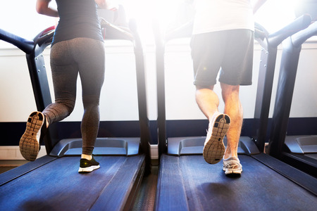 in behind: Lower Body Shot of Healthy Athletic Couple Running on Treadmill Machine Inside the Fitness Gym Stock Photo