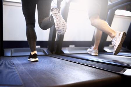 건강한 젊은 커플의 톤 다리 피트니스 체육관 내부 러닝 머신 장치에 운동.