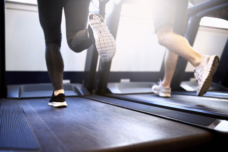 treadmill: Toned Legs of Healthy Young Couple Exercising on Treadmill Device Inside Fitness Gym.