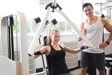 cardiovascular exercising: Handsome Male Fitness Trainer Smiling at the Camera while Assisting a Healthy Woman Doing Chest Press Exercise in the Gym.