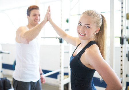 fitness goal: Blond Woman Looking Over Shoulder at Camera and High Fiving Male Trainer in Gym, Celebrating Accomplishment of Fitness Goal