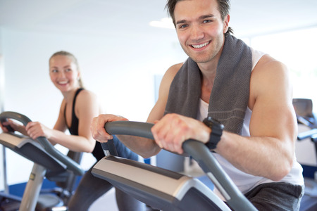 gym workout: Handsome Muscular Young Guy Smiling at the Camera, While Exercising on Elliptical Bike, with his Partner Next to him Inside the Fitness Gym.