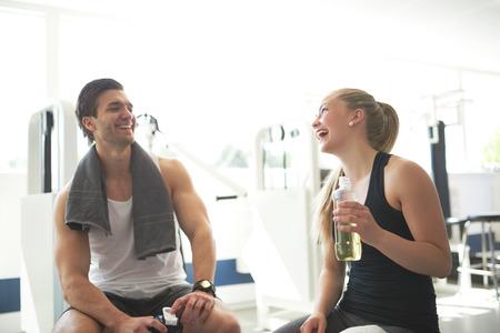 gestos de la cara: Pareja sana joven que se relaja después de entrenamiento en el gimnasio con felices expresiones faciales. Foto de archivo