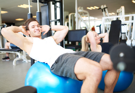 pilates man: Handsome Young Fit Guy Smiling at the Camera While Doing Sit-ups on Exercise Ball Inside the Gym.