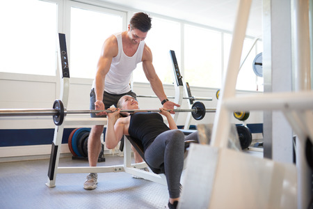 man gym: Athletic Young Gym Instructor Guy Supporting a Fit Woman Student in Lifting Barbell Exercise Inside the Gym