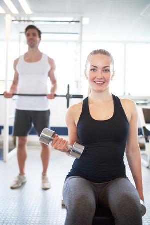 woman working: Smiling Blond Woman Lifting Hand Weights in Seated Position in Brightly Lit Gym with Man Lifting Barbell in Background Stock Photo