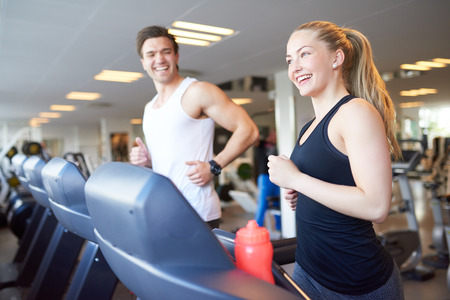 gym: Healthy Young Couple Doing Running Exercise on Treadmill Device Inside the Gym with Happy Facial Expressions.